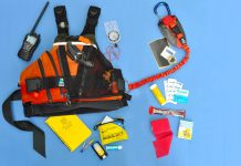 a PFD surrounded by safety gear such as a radio, a first aid kit, a whistel, sunscreen, a notepad and other gear to complete the kit.