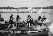 several young women hugging each other surrounded by canoes in Algonquin Park, Ontario.