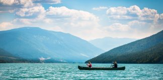 two people paddling a canoe on Lake Revelstoke surrounded by mountains
