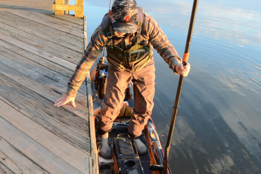 angler getting into his fishing kayak from the dock