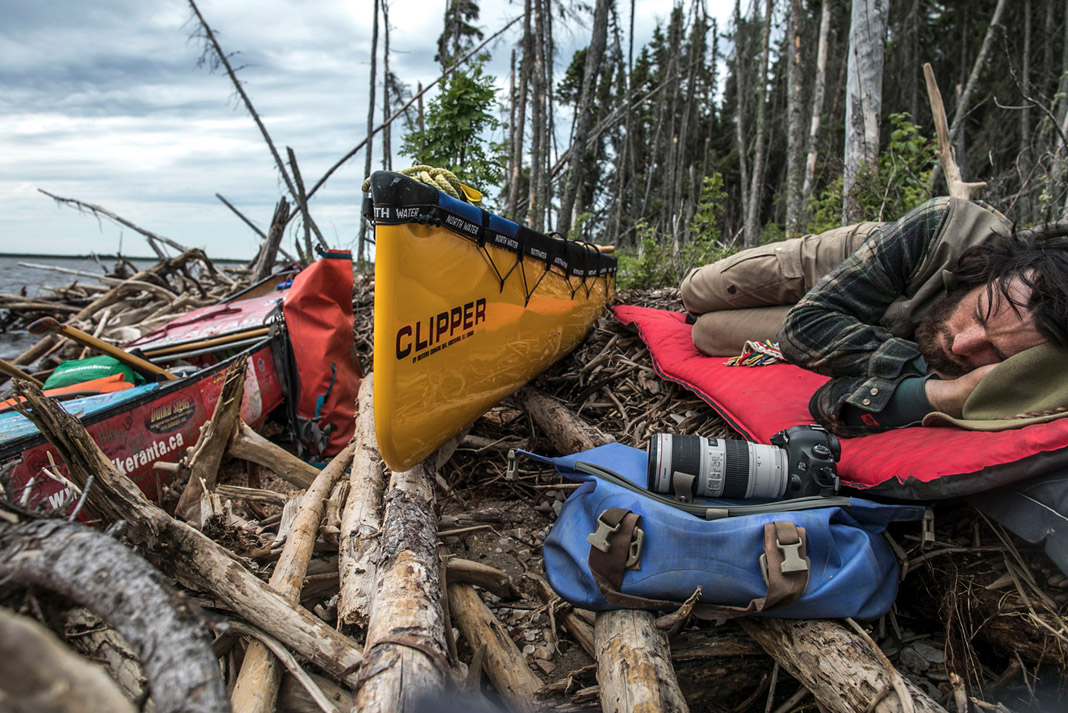 man sleeping next to his canoe surrounded by paddling and photography gear