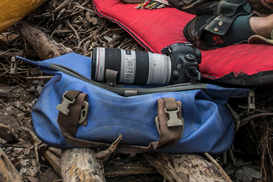 camera laying on several duffle bags