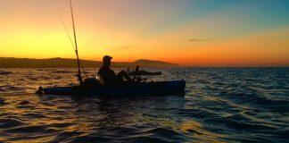 fisherman on his fishing kayak at sunset
