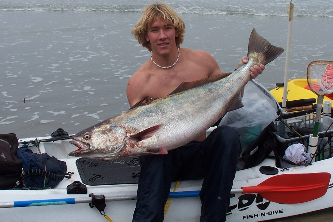 young man holding a large fish sitting in a cobra fishing kayak