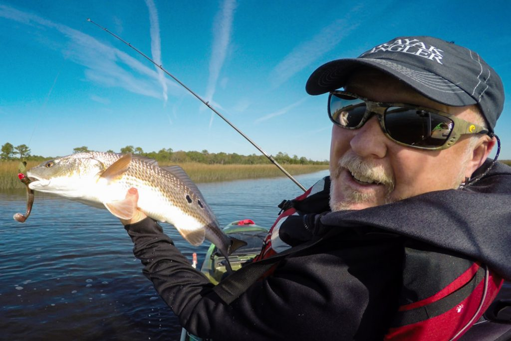 angler holding a large redfish on his kayak