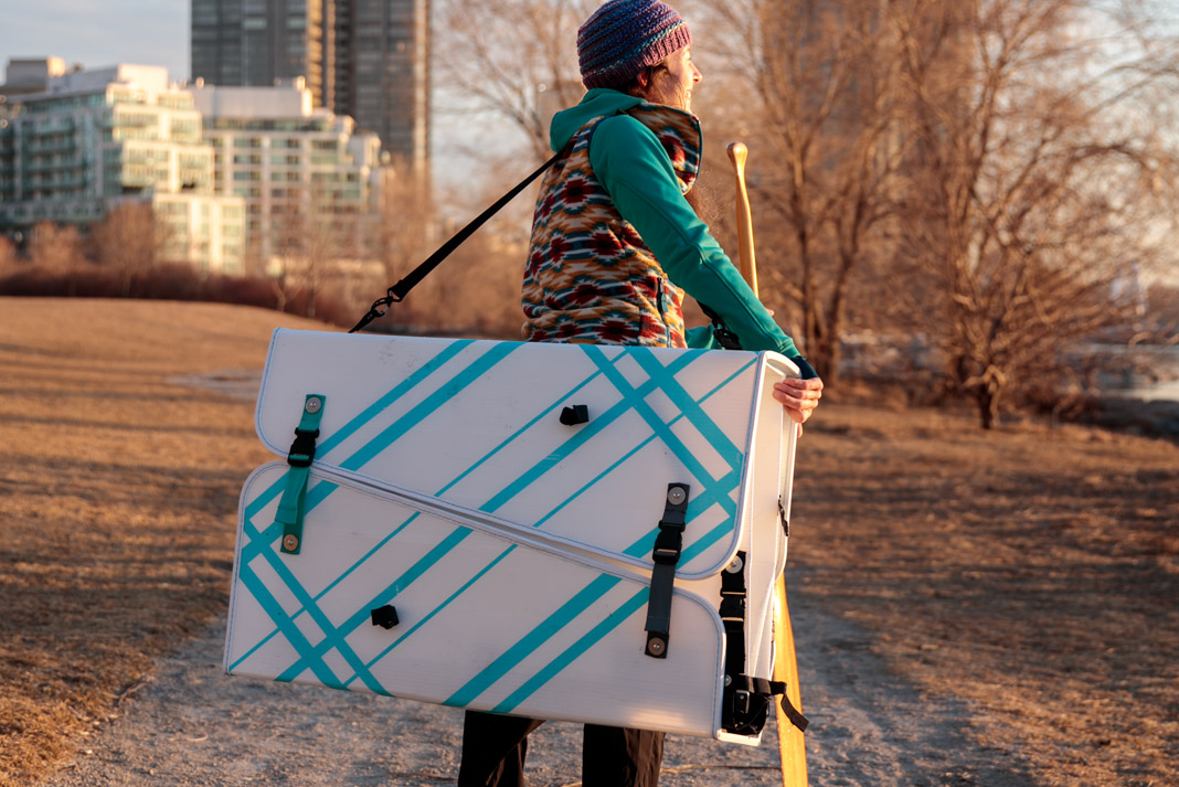 Kaydi Pyette carrying MyCanoe's Plus Model folding canoe and a wooden paddle in Toronto, Ontario, Canada.