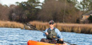 man paddling an orange native watercraft fishing kayak