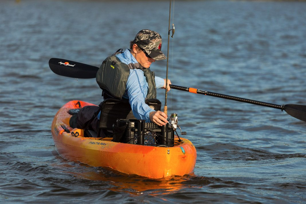 man adjusting his fishing pole in orange native craft kayak