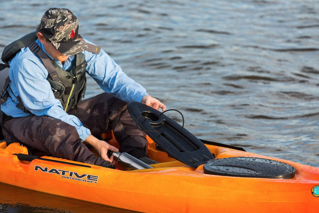 man storing water bottle in his orange fishing kayak