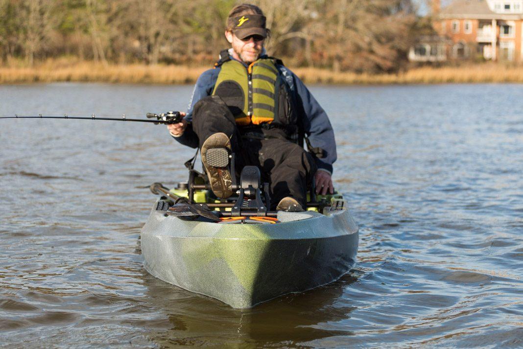 a man pedaling a kayak and fishing