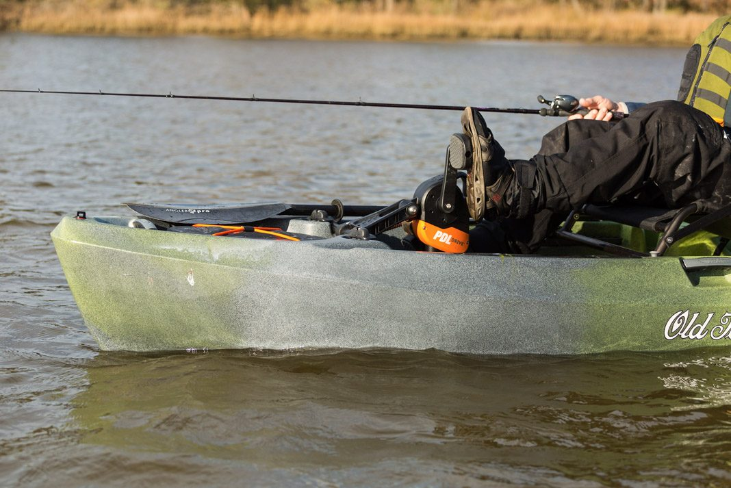 a man with his feet on the pedals inside his fishing kayak