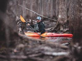 man paddling a sit inside fishing kayak