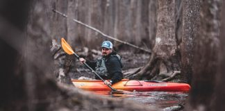 man paddling a sit inside fishing kayak
