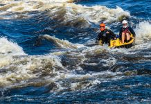 two men pedal boating in whitewater