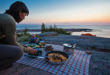 A camper prepares dinner on the rocky edge of a large body of water, late in the evening