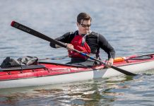 Kayaker paddles while being hooked up to force sensors collecting data