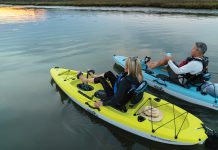 A young couple are seen pedalling around each in a Hobie Mirage Passport kayak