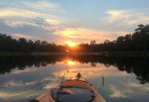 A kayak angler fishing during sunset while camping
