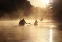 Canoeists paddle into a misty morning on the lake