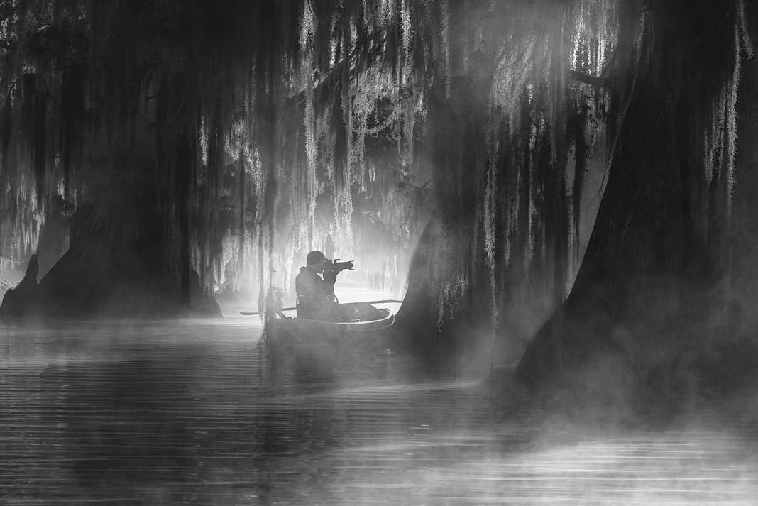 a man on his kayak photographing a swamp in Louisiana's Atchafalaya Basin