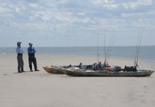 Two anglers about to launch kayaks into ocean