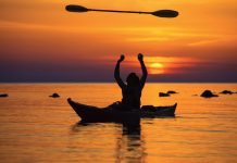 a kayaker tossing up their kayak paddle with the sun setting in the background on calm waters