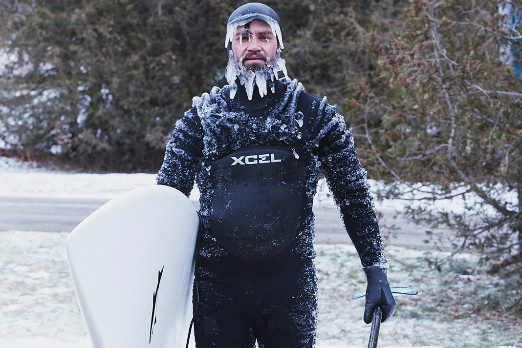 man standing with his paddleboard in the winter covered with icicles on his face