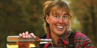 Virginia Marshall smiling while pouring wine into a cup wearing her paddling gear