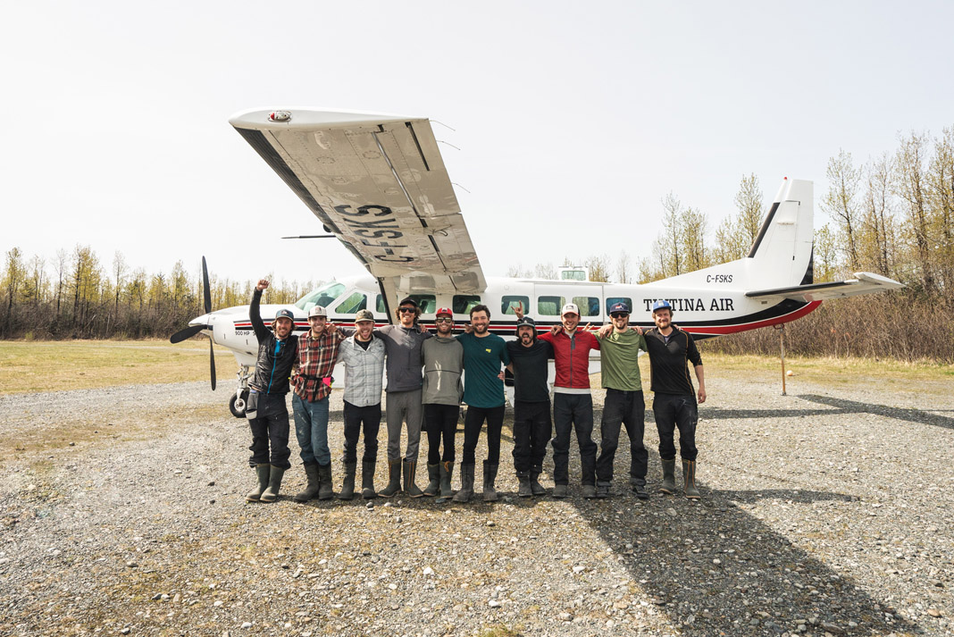 10 men standing in front of a small aircraft