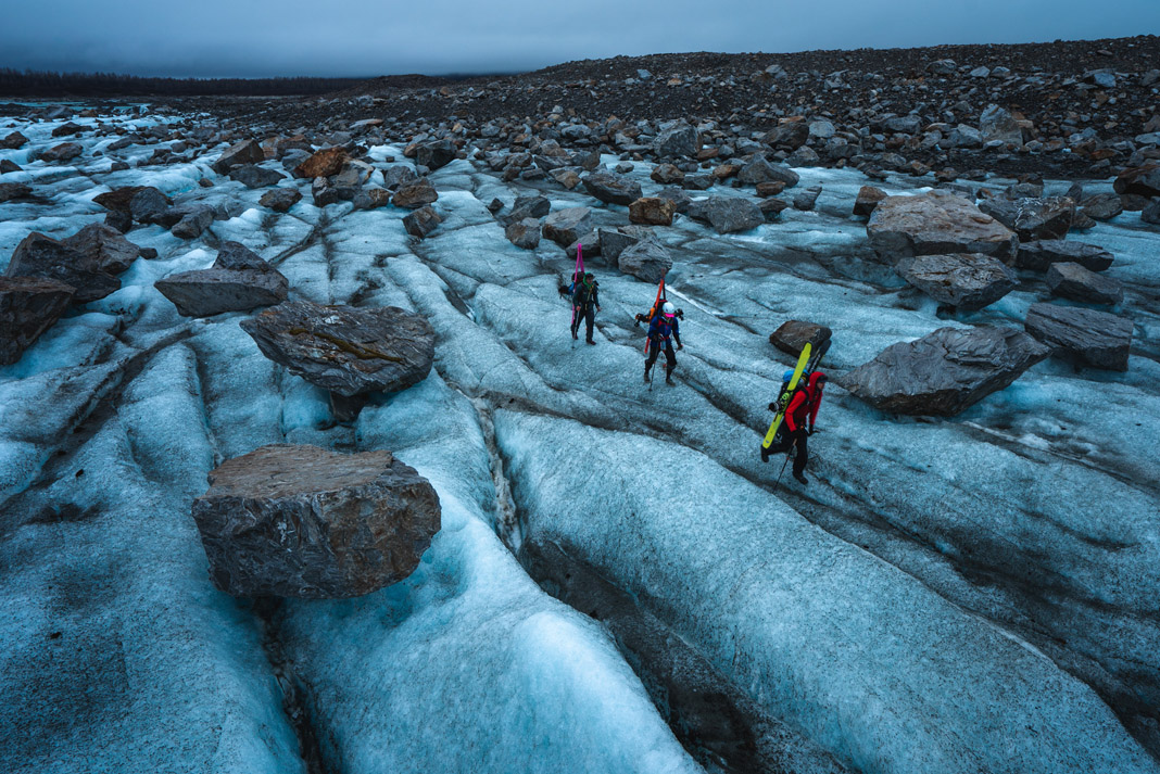 three men walking with skis on their back beside massive rocks on a glacier