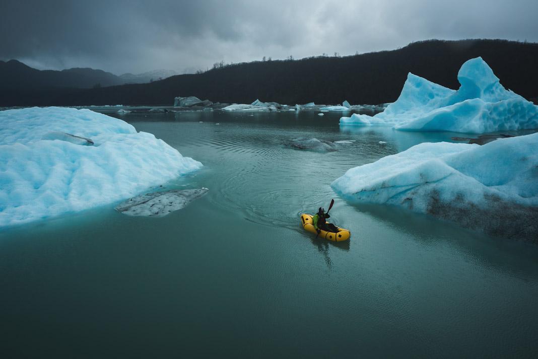 man paddling his blow up kayak through ice bergs