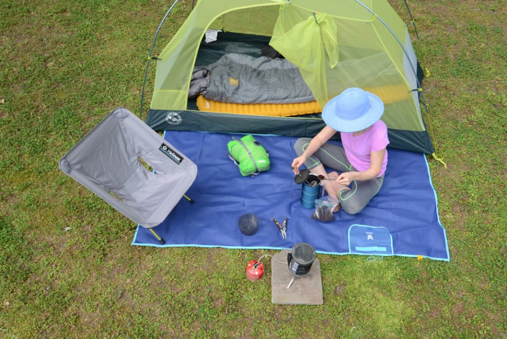 Kayak angler sits next to tent on camping trip