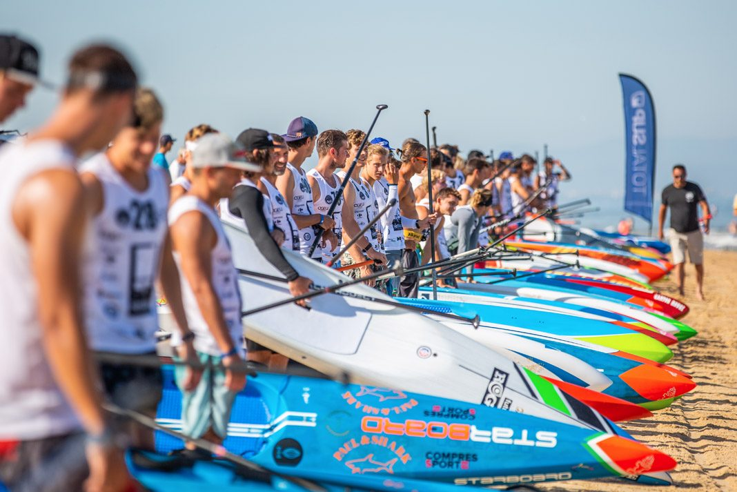 several standup paddleboarding athletes standing in a line