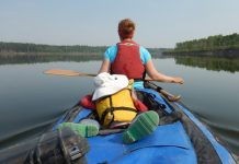 A child lies in a canoe while his mother paddles in the bow.