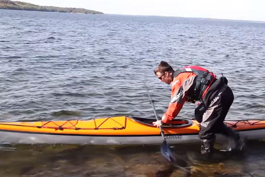 Steve Ruskay standing knee deep in water, launching a kayak.