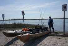 Angler loads his kayak with crates before setting off into the ocean