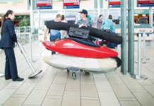two men pushing a cart in the airport with their kayaks and kayak paddles