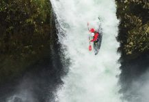 a kayaker hucking off a waterfall in his kayak