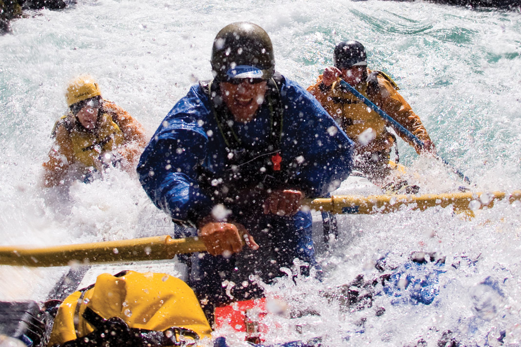 a river guide taking clients down the river in a yellow raft, smiling while smashing through whitewater