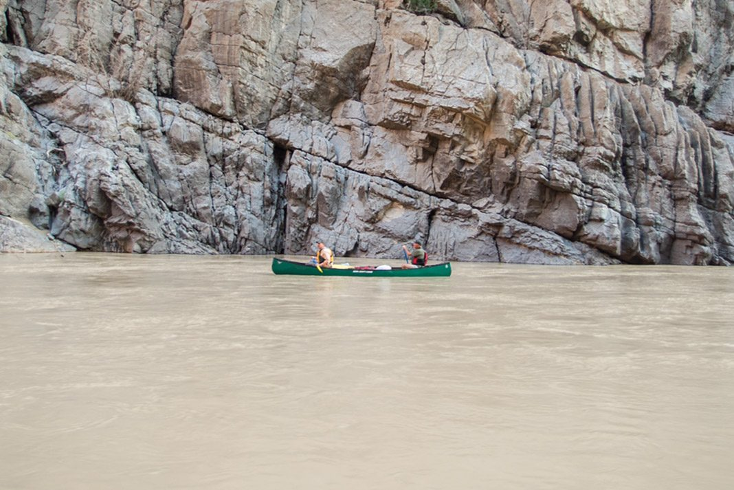 two men paddling a canoe on calm waters of the Grand Canyon