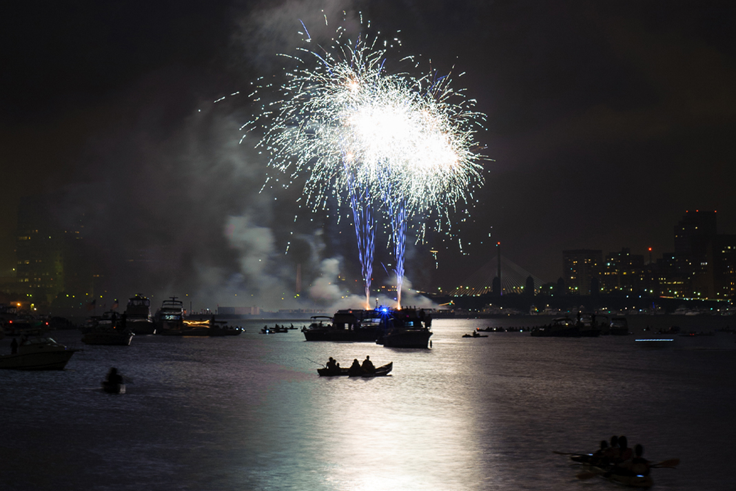 Kayakers and boaters enjoy the Fourth of July fireworks display on the the Boston Harbor.