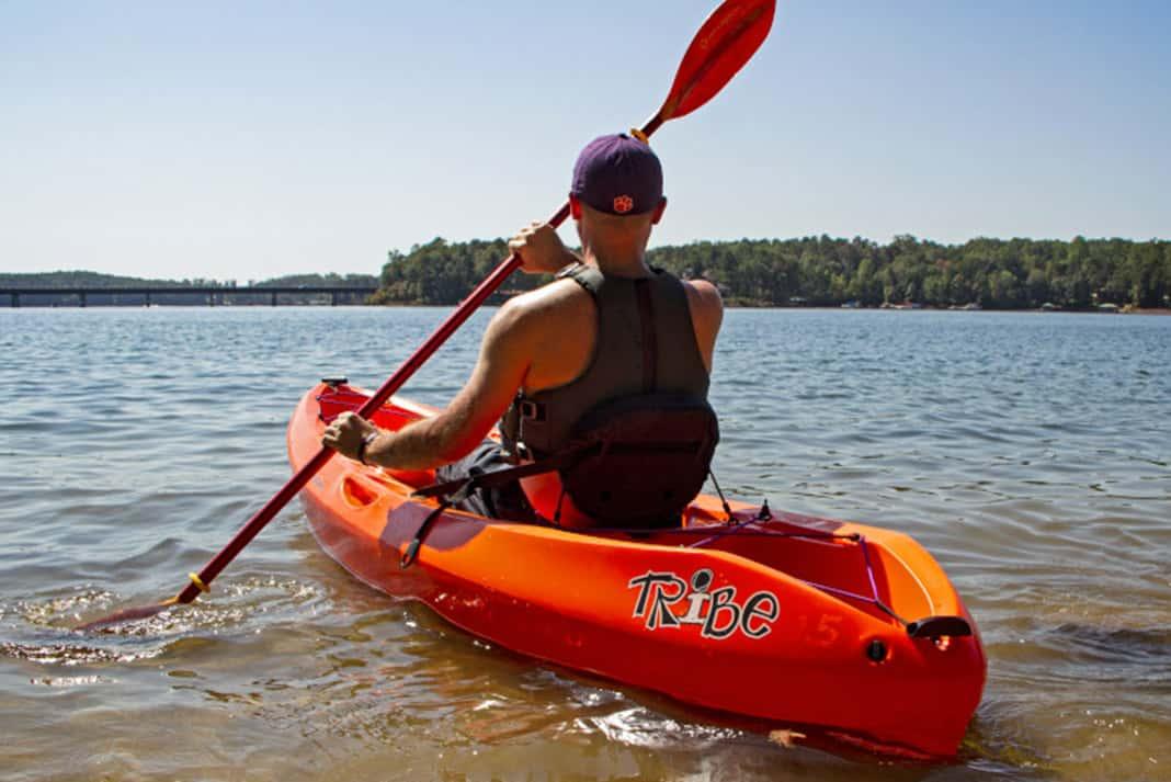 Man paddling orange kayak