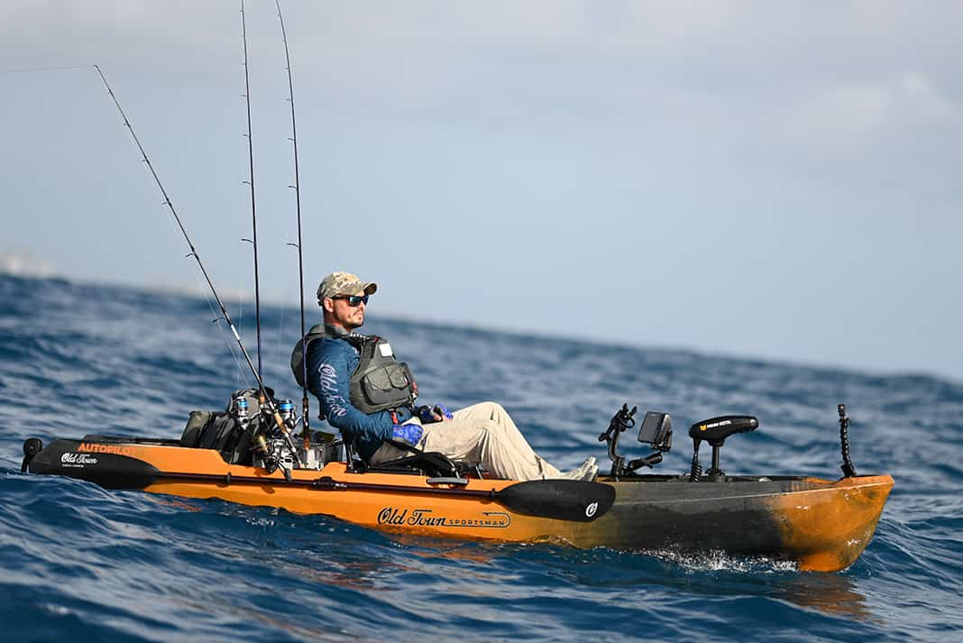 Man riding out the waves in a fishing kayak.