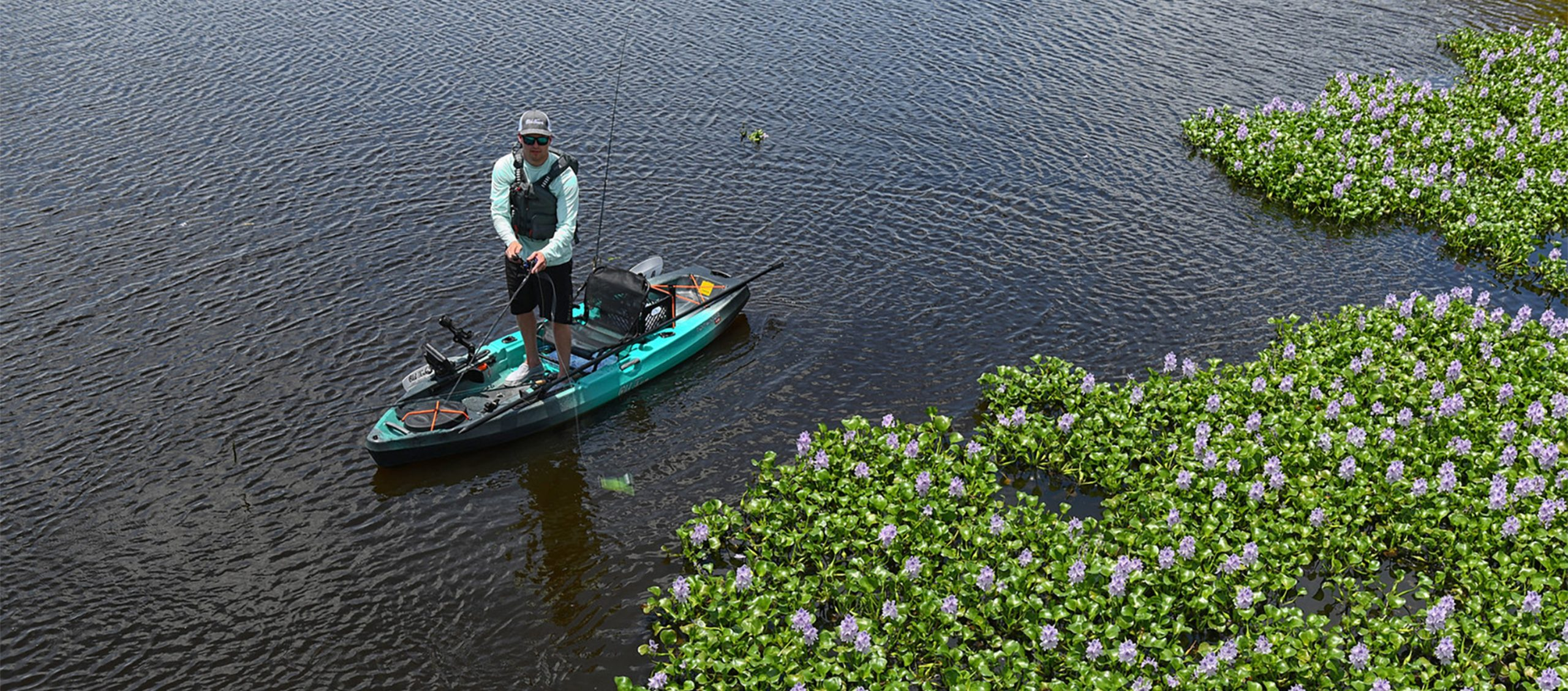 Man standing up on sit-on-top fishing kayak with a fishing rod
