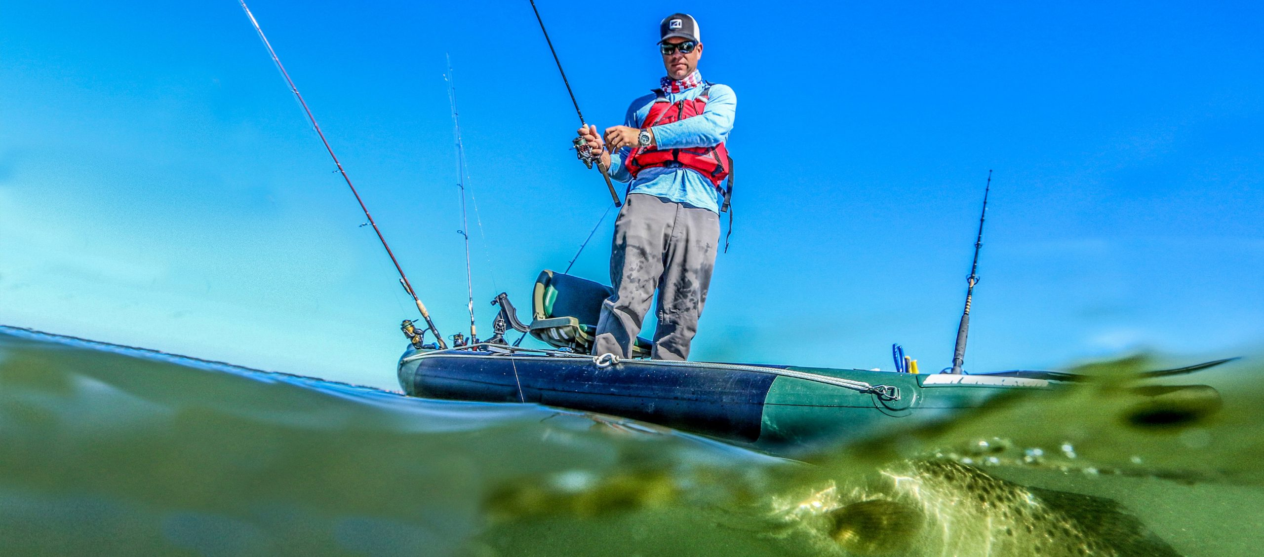 Man standing up on fishing kayak with fish just below the surface