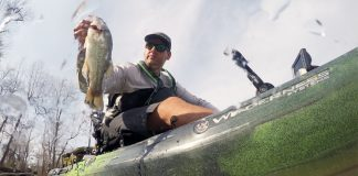 Low angle of man sitting on sit-on-top fishing kayak and lifting a fish out of the water.