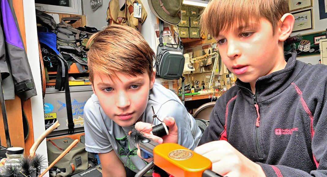 Two boys look at their first fishing lure set up