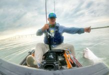 A kayak fisherman lands a fish on the ocean