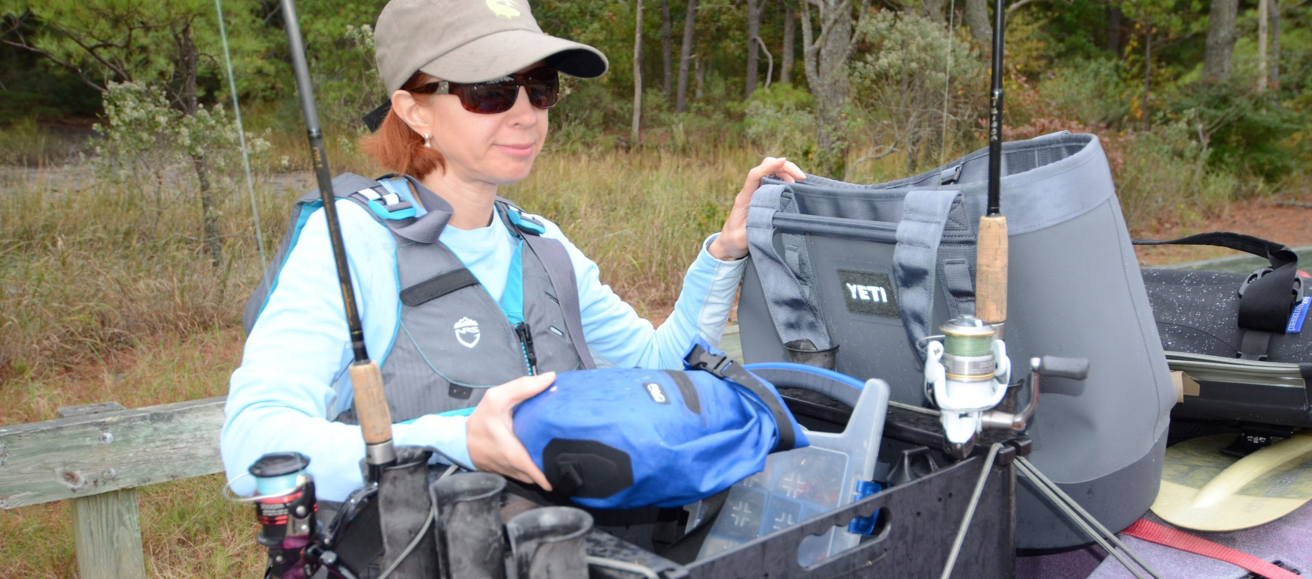 Woman standing beside fishing kayak with cooler, drybag, and other gear.