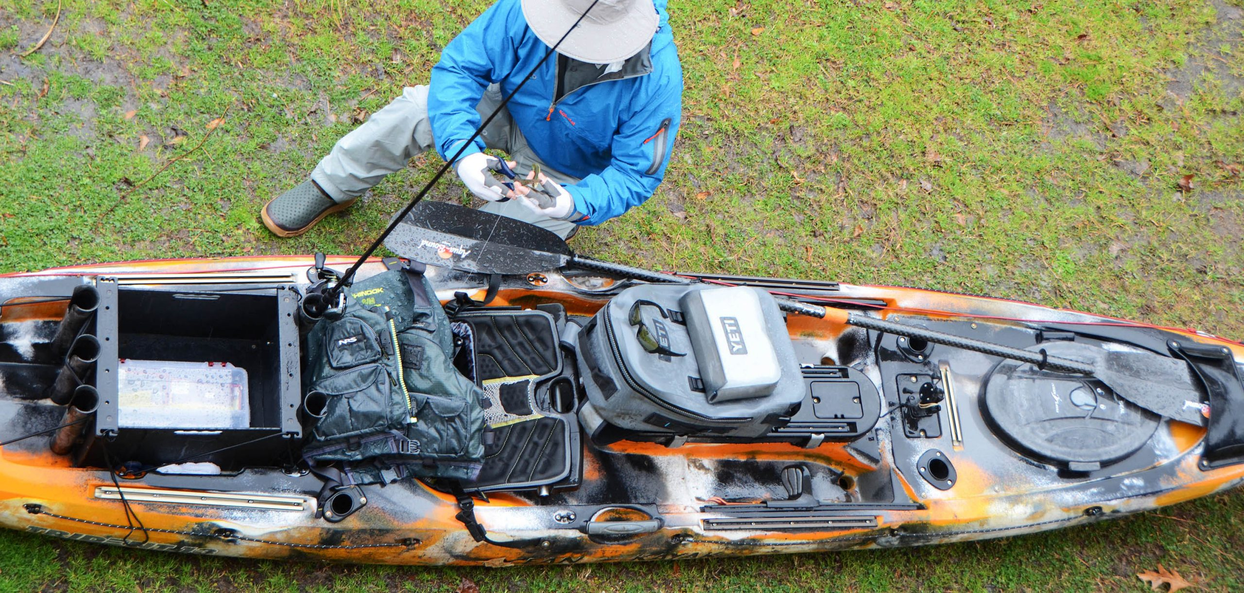 Overhead view of angler getting their fishing kayak ready on land.